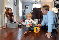 DOYLESTOWN, PA -  DECEMBER 16:  From left, Patty Pharr, her son Oliver Pharr and therapist Janet McGinchey play on new floor the homeowner won from Barb - Lin flooring December 16, 2013 in Doylestown, Pennsylvania. (Photo by William Thomas Cain/Cain Images)
