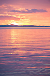 Misool, Raja Ampat, Indonesia; a pink and purple sunset reflecting in the Ceram Sea