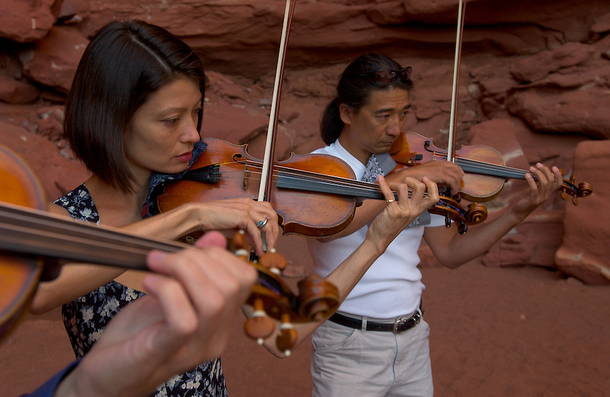 Violinists Laura Frautschi, center, and L.P. How tune for an orchestral music concert at a natural red rock grotto in a Colorado River canyon wall, for the Moab Music Festival in Moab, Utah, Thursday, Sept. 16, 2004. Performers also included Paquito D'Rivera, Paul Hersh and Mark Summer. (Kevin Moloney for the New York Times)