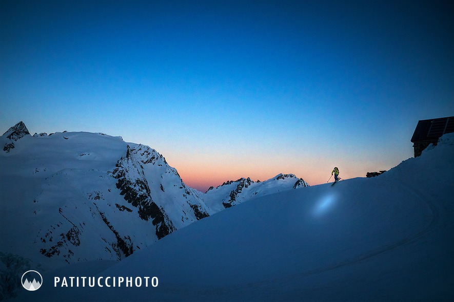 A skier leaves the Trift Hut at dawn with a headlamp on while on a ski tour of the Berner Haute Route, Switzerland