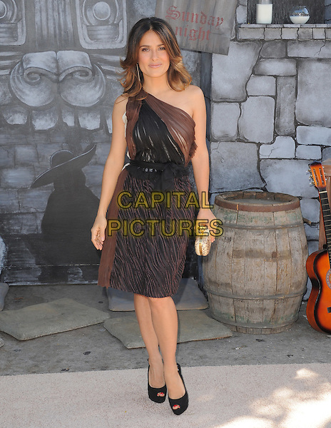 Salma Hayek .The L.A. Premiere of 'Puss in Boots' held at The Regency Village  Theatre in Westwood, California, USA..October 23rd, 2011 .full length dress black brown sheer one shoulder gold clutch bag  .CAP/RKE/DVS.©DVS/RockinExposures/Capital Pictures.