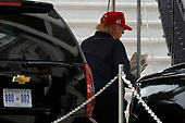 United States President Donald J. Trump holds newspapers as he returns to the White House in Washington after playing golf at Trump National Golf Club on October 13, 2019. <br /> Credit: Yuri Gripas / Pool via CNP