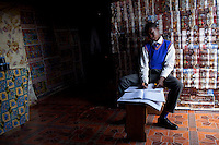 KHUTSONG, SOUTH AFRICA - OCTOBER 16: Bafana Mashata, age 17, does his home work in the family tin shack on October 16, 2012, in Khutsong, South Africa. Khutsong, a black township. is located about 56 miles west of Johannesburg, and surrounded by gold mines. Because of recent strikes many mineworkers has been fired which is making the poverty worse here. (Photo by Per-Anders Pettersson)