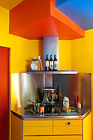In a space-saving measure the cooker and stainless steel hob have been built into a corner of the bright yellow kitchen