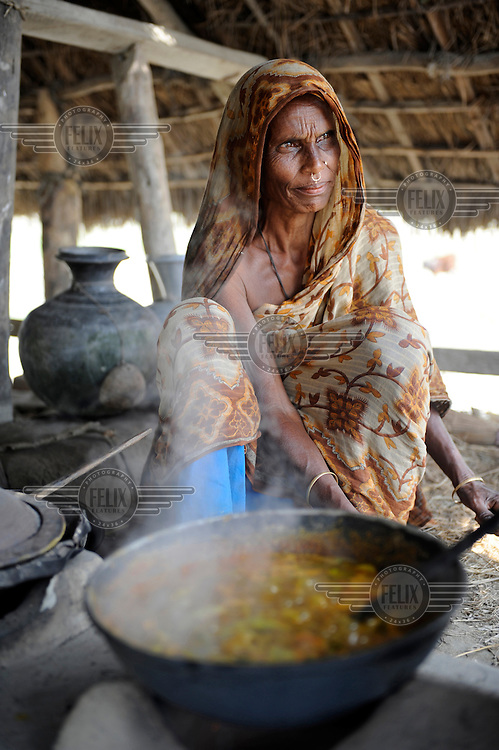 A woman cooks food on an island in Patuakhali district that was devestated by Cyclone Nargis. The region is known for its annual floods, which prevents necessary investment in the area. As water levels continue to rise, villagers will soon have to find another place to live.