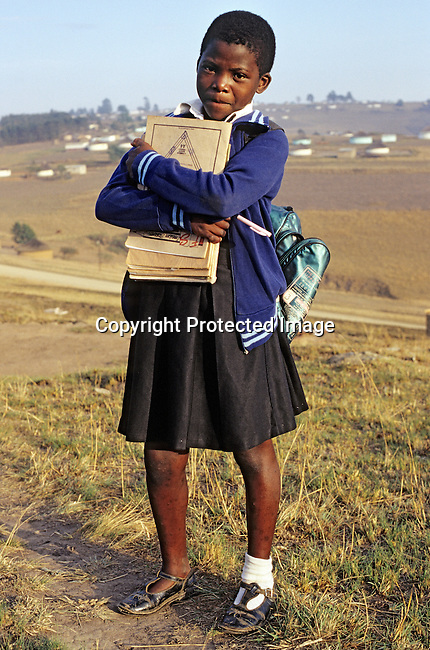 An unidentified girl walks to school on November 28, 2000 in Nqbeni a rural area in Natal, South Africa. The girl lives in one the poorest areas of the country and many families cannot afford to send their children to school as school fees, uniforms and books are expensive. About 5,6 million South Africans are living with HIV/Aids and its estimated that about one thousand people die every day to Aids related diseases. (Photo by: Per-Anders Pettersson)