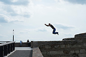Parkour specialist practices a wall-to-wall leap, Buda Castle, Budapest.