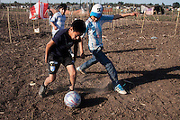 Un grupo de niños juegan futboll , en el  asentamiento, ubicado en la periferia de la ciudad de Tucumán, al Noroeste de Argentina; donde unas mil quinientas familias con dificultad para acceder a una vivienda propia tomaron posición de un campo que pertenece al ingenio Concepción. As one more face of  the housing problems in Argentina, about 1,500 families invaded a large piece of land belonging to a sugar cane plantation and factory, Concepcion, in the Northern province of Tucuman. After a decade of strong economic growing, Argentina is still showing high levels of poverty and underdevolpment.