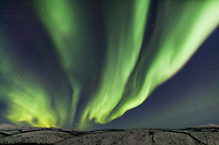 Aurora borealis arcs over the White Mountains in the White Mountains National Recreation Area, Interior, Alaska.