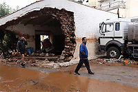 Pictured: A man walks past a partially collapsed building.<br />