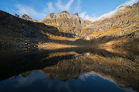 Trolldalstind mountain peak rises over lake Trolldalsvatnet in autumn, Moskenesøy, Lofoten Islands, Norway