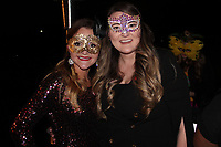 NWA Democrat-Gazette/CARIN SCHOPPMEYER Brittney Skelton (left) and Kimberly Short, Moonlight Masquerade committee members, welcome guests to the Junior League benefit.