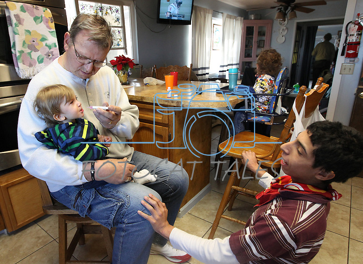 Merrill Simon gives teething medicine to Montana, 1, while talking about football with Mordachi, 15, on Sunday, Dec. 11, 2011 in Mound House, Nev. Simon and his wife Roberta have adopted 21 special needs foster kids over the years. .Photo by Cathleen Allison