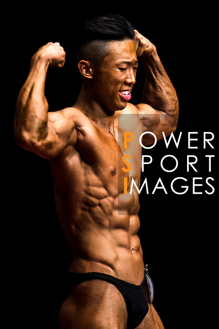 Wong ho Ming flexes muscles for judges on stage during the Hong Kong Bodybuilding Championship on 29 June 2014 at the Queen Elizabeth Stadium Arena in Hong Kong, China. Photo by Aitor Alcalde /  Power Sport Images