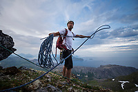 Male climber prepares rope for rappel from summit of Stjerntind mountai peak, Flakstadøy, Lofoten Islands, Norway