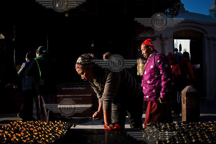 A Tibetan refugee lights lamps at the holy site of Boudhanath.