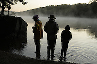 Woodford, VT, USA - August 21, 2008: Early morning mist rises from a lake atop the Green Mountains of southern Vermont as a mother and daughters walk along the shore
