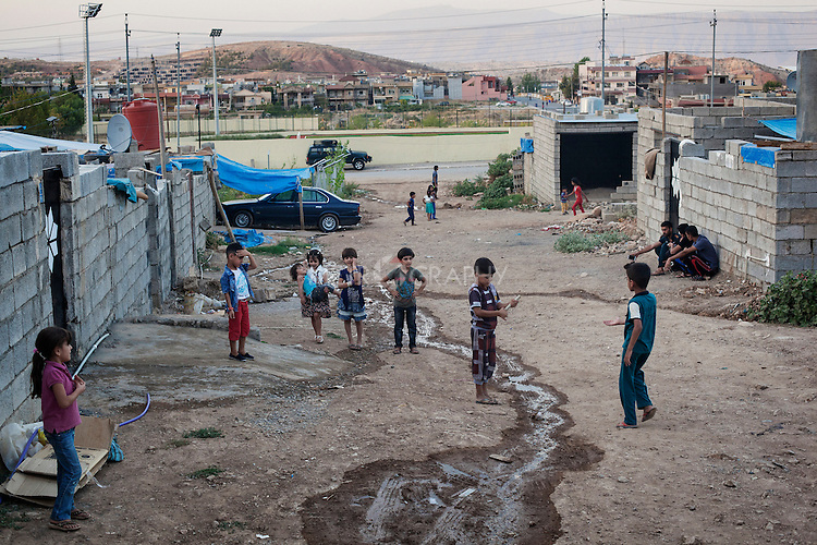 26/08/15. Shaqlawa, Iraq. -- Displaced children from Al Anbar province play at dusk, outside their houses in Seirmaidan. 11 families live in this neighborhood (Tajawaz area), where they rent small houses from Kurdish families. Each small house comprises of a bedroom and a kitchen and cost about 350.000 IQD per month. The houses were built by the owners without authorization from the municipality and are deemed inhabitable.
