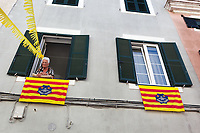 "Spain. Balearic Islands. Minorca (Menorca). Mahon. An elderly woman looks out her flat's window at the parade of the Giants in the ""Festes de la Mare de Déu de Gràcia"" during the traditional summer festival. Colorful festive bunting across street. Two flags of Menorca are fixed on the wall. The flag of Menorca was adopted on 14 November 1983. It is based on and is the predominantly red and yellow Catalan-Aragonese (Senyera) flag with the coat-of-arms of Menorca. Maó (in Catalan) and Mahón (in Spanish), written in English as Mahon, is a municipality, the capital city of the island of Menorca, and seat of the Island Council of Menorca. The city is located on the eastern coast of the island, which is part of the autonomous community of the Balearic. In Spain, an autonomous community is a first-level political and administrative division, created in accordance with the Spanish constitution of 1978, with the aim of guaranteeing limited autonomy of the nationalities and regions that make up Spain. 7.09.2019 © 2019 Didier Ruef"