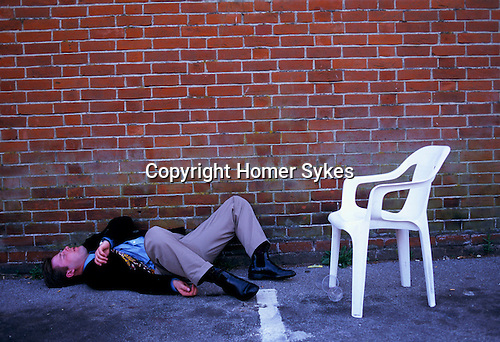 DRUNK MAN LYING ON FLOOR, PASSED OUT, AT THE DERBY HORSE RACES,