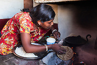 Nitu (not her real name), cooks in her kitchen in Jhaju village, Bikaner, Rajasthan, India on 4th October 2012. Now 18, she was married off at age 10 to a boy of around the same age, but only went to live with her in-laws when she was 12, after she had finished studying up to class 6. The three sisters, aged 10, 12, and 15 were married off on the same day by their maternal grandfather while their father was hospitalized. She was abused by her young husband and in-laws so her father took her back after hearing that her husband, who works in a brick kiln, was an alcoholic and was doing drugs and crime. She had only spent a few days at her husband's house at that time. Her father (now out of the hospital) has said that she will only be allowed to return to her husband's house if he changes his ways but so far, the negotiations are still underway. Photo by Suzanne Lee for PLAN UK