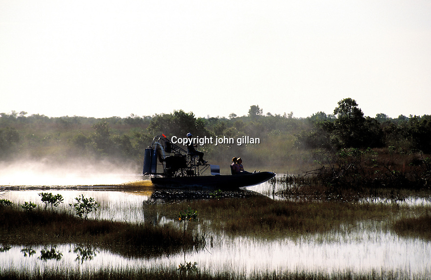 Silhouette of an airboat in the swamp with a driver and 2 passengers.