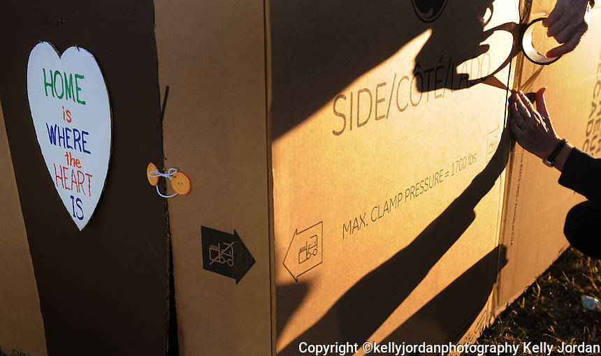"Kelly.Jordan@jacksonville.com--111111--Lynette Weber, of Jacksonville is casts a shadow across her cardboard box home as she puts the finishing touches on her home as the sun sets. In an effort to raise money and bring awareness to homelessness Family Promise of Jax hosted Cardboard City, an opportunity for participants to experience what it is like to be homeless by sleeping in cardboard boxes Friday night, November 11, 2011. Despite a chilly forecast, participants set up their cardboard box houses at the CrossRoad Church on Gate Parkway on the Southside. This is the first time Weber has participated in the event, and says, ""I was thinking one whole night in the cold, I'm going to freeze. But I realized that every night they (the homeless) do.""(The Florida Times-Union, Kelly Jordan)"