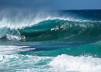 Surfer getting barrelled on a big wave at the 2011 Billabong Pro Pipe Masters surfing contest, Banzai Pipeline, North Shore, O'ahu