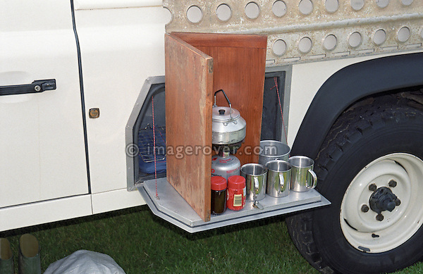Side locker of Land Rover Defender 110 Hardtop containing a gas stove, tea kettle, and mugs to have some tea. --- No releases available. Automotive trademarks are the property of the trademark holder, authorization may be needed for some uses.