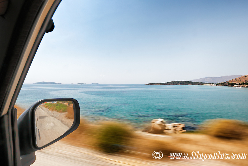 The view through the window from the perspective of the passenger in a moving car traveling around Andros, Greece