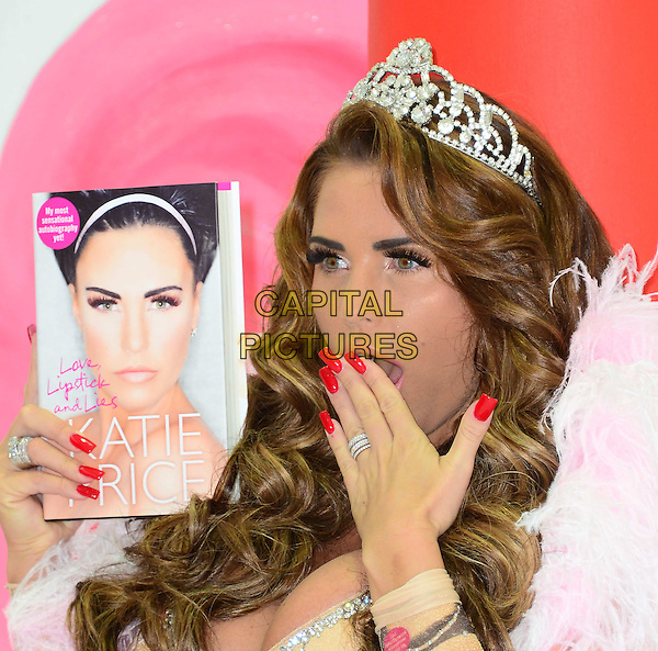 Katie Price (aka Jordan)<br /> At a photocall to launch her autobiography - 'Love, Lipstick And Lies' at The Worx, London, England.<br /> October 22nd, 2013<br /> headshot portrait cover print crown tiara  beige silver cleavage  red nail varnish polish mouth open looks surprised shocked<br /> CAP/BF<br /> &copy;Bob Fidgeon/Capital Pictures