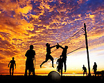 A beach volleyball game takes place under a November sunset at Shell Point in Wakulla County south of Tallahassee. Florida.