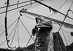 Malcolm Smitheram, deckhand and cook, securing the nets, on PZ 198, the 'Aaltje Adriaantje', working out of Newlyn, Cornwall, England.<br />