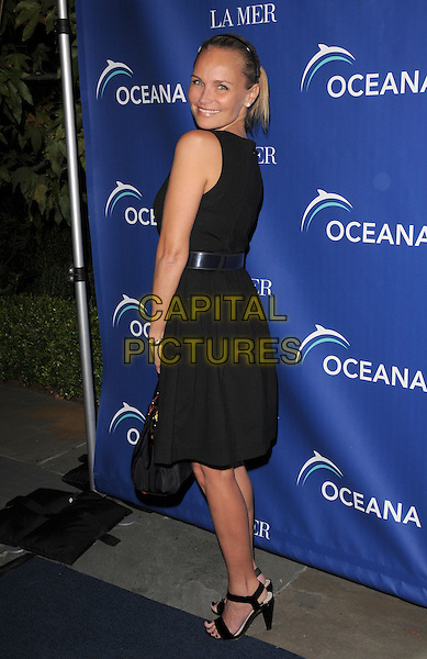 KRISTIN CHENOWETH .at Oceana's Annual Partners Award Gala held at a private residence in Pacific Palisades, California, USA, October 18th 2008.                                                                     .full length black sleeveless dress sandals bag belt looking back over shoulder .CAP/DVS.©Debbie VanStory/Capital Pictures