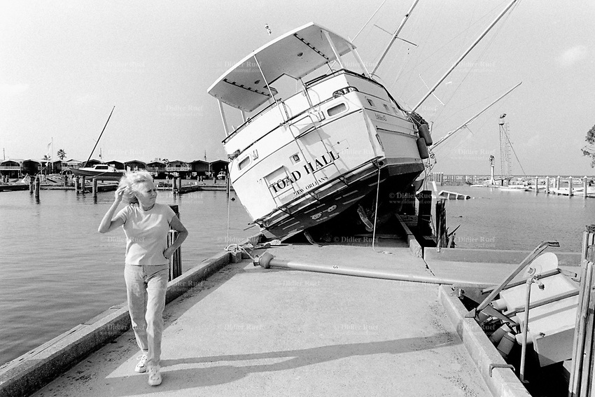 USA. Louisiana. New Orleans. Orleans Parish. Orleans marina. Southern Yacht Club. Aftermath of hurricane Katrina. Due to the strength of the storm and a tidal surge, a pleasure boat lays on the pier of the harbour. A woman checks the level of destruction. Maritime waste. © 2005 Didier Ruef