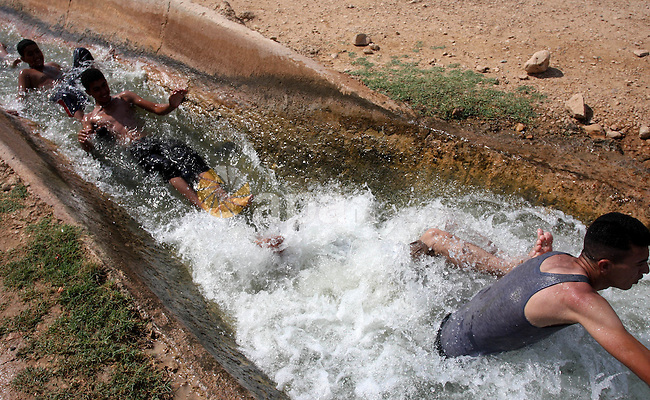 Palestinians cool off in the water of a natural spring known as Ein al-Auja, near the West Bank city of Jericho June 16, 2012. Photo by Issam Rimawi