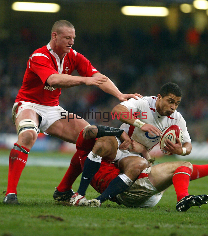 Gareth Thomas hauls down his opposite number Jason Robinson.RBS 6 Nations.Wales v England.Millennium Stadium.05.02.05.©Steve Pope.Sportingwales.com.07798 83 00 89.The Manor .Coldra Woods.Newport.South Wales.NP18 1HQ