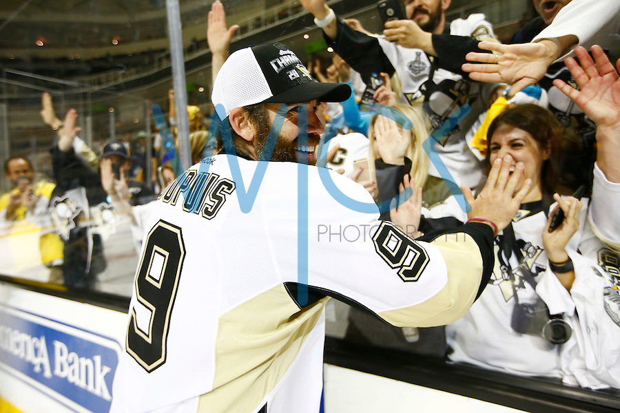 Pascal Dupuis #9 of the Pittsburgh Penguins celebrates with the fans along the glass following their 3-1 win against the San Jose Sharks during game six of the Stanley Cup Final at SAP Center in San Jose, California on June 12, 2016. (Photo by Jared Wickerham / DKPS)