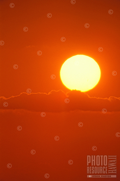 A blazing white hot sun rests on a finger cloud starkly contrasted against a burnt orange sky.