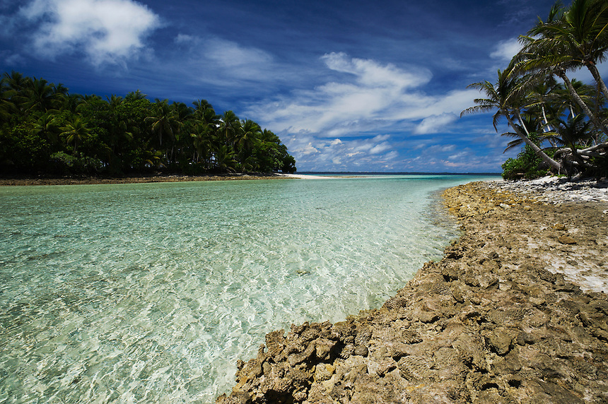 The tropical waters of the Pacific Ocean flow into the Majuro Lagoon at high tide near Eneko Island.