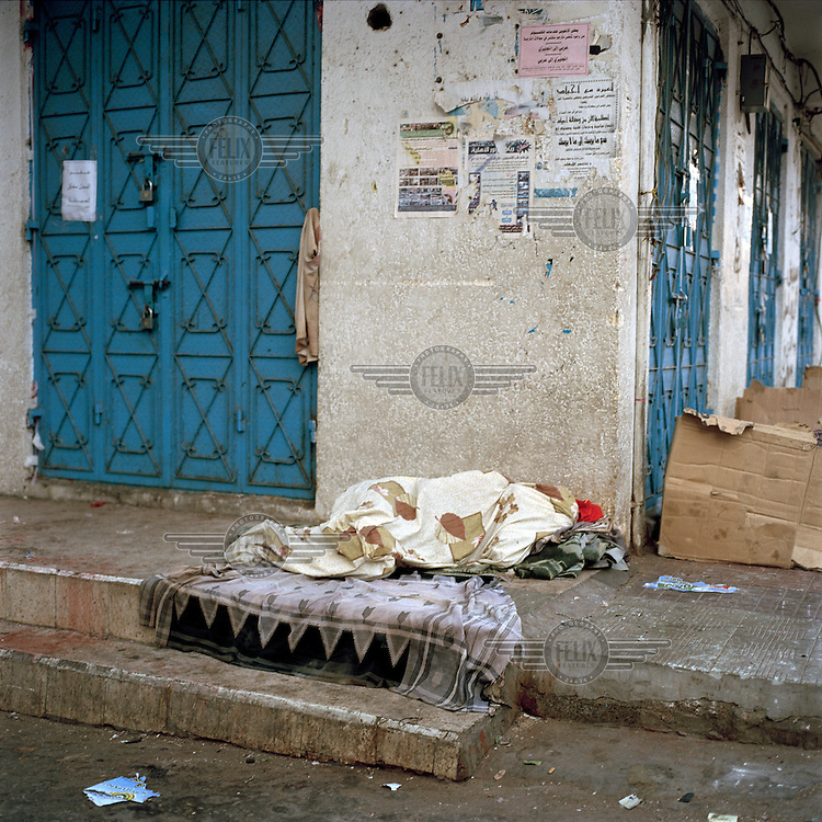 A migrant worker sleeps on the pavement near to the main mosque..