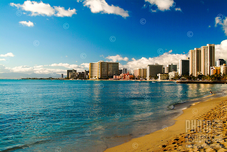 The hotel lined strip of Waikiki Beach with sand and calm ocean in the foreground.