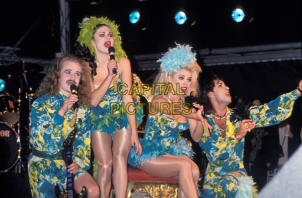 ARMY OF LOVERS.London, circa 1990's.half length band group gig music record blonde big hair make up red lips mustache yellow green blue outfits plunge neckline dress trousers shorts shirts stage feathers stage singing.www.capitalpictures.com.sales@capitalpictures.com.©Capital Pictures