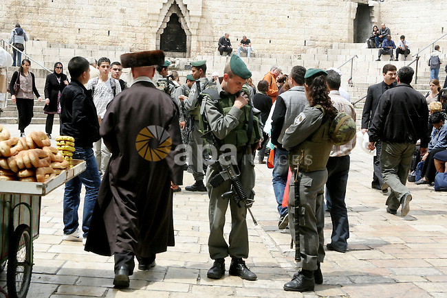 Palestinians walk past an Israeli police officers as they stand guards in the market of the old city of Jerusalem on April 21,2011 photo by MAhfouz Abu Turk