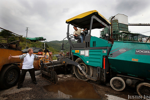 Ulrich Reichert, managing director of German heavy machinery manufacturer Wirtgen, instructing a driver of his asphalt paving machine in Hong Kong to extend the asphalt paving component. It is this component for which .Reichert was falsely accused of breaking Chinese customs rules and imprisoned for six weeks in China. The case against him subsequently collapsed.