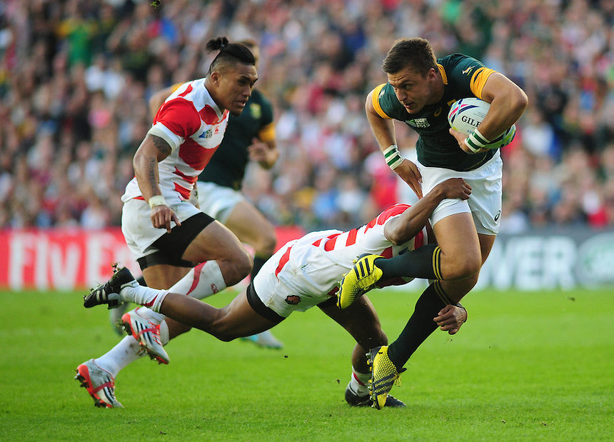 South Africa's Handre Pollard is tackled by Japan's Kotaro Matsushima<br /> <br /> Photographer Kevin Barnes/CameraSport<br /> <br /> Rugby Union - 2015 Rugby World Cup - Japan v South Africa - Saturday 19th September 2015 - The American Express Community Stadium - Falmer - Brighton<br /> <br /> &copy; CameraSport - 43 Linden Ave. Countesthorpe. Leicester. England. LE8 5PG - Tel: +44 (0) 116 277 4147 - admin@camerasport.com - www.camerasport.com