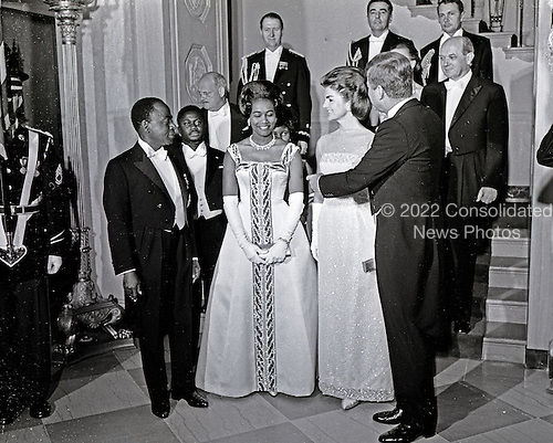 United States President John F. Kennedy and First Lady Jacqueline Kennedy stand in front of the Grand Staircase of the White House in Washington, DC prior to a dinner in honor of President of the Ivory Coast, F&eacute;lix Houphou&euml;t-Boigny, and First Lady of the Ivory Coast, Marie-Th&eacute;r&egrave;se Houphou&euml;t-Boigny on May 22, 1962. Front row (L-R): President Houphou&euml;t-Boigny; Mrs. Houphou&euml;t-Boigny; Mrs. Kennedy; President Kennedy. Others (L-R): Ambassador of the Ivory Coast, Henri Konan B&eacute;di&eacute;; U.S. Ambassador to the Ivory Coast, R. Borden Reams; Military Aide to President Kennedy, General Chester V. Clifton; Air Force Aide to President Kennedy, Brigadier General Godfrey T. McHugh; Virginia Rusk (mostly hidden); U.S. Secretary of State Dean Rusk ; Naval Aide to President Kennedy, Captain Tazewell Shepard. <br /> Credit: Arnie Sachs / CNP