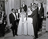 United States President John F. Kennedy and First Lady Jacqueline Kennedy stand in front of the Grand Staircase of the White House in Washington, DC prior to a dinner in honor of President of the Ivory Coast, Félix Houphouët-Boigny, and First Lady of the Ivory Coast, Marie-Thérèse Houphouët-Boigny on May 22, 1962. Front row (L-R): President Houphouët-Boigny; Mrs. Houphouët-Boigny; Mrs. Kennedy; President Kennedy. Others (L-R): Ambassador of the Ivory Coast, Henri Konan Bédié; U.S. Ambassador to the Ivory Coast, R. Borden Reams; Military Aide to President Kennedy, General Chester V. Clifton; Air Force Aide to President Kennedy, Brigadier General Godfrey T. McHugh; Virginia Rusk (mostly hidden); U.S. Secretary of State Dean Rusk ; Naval Aide to President Kennedy, Captain Tazewell Shepard. <br /> Credit: Arnie Sachs / CNP