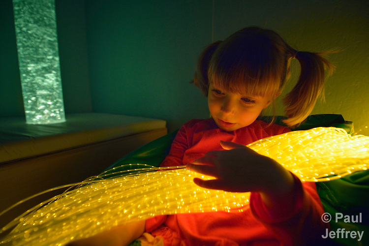 Four-year old Karis Andrews enjoys the LED strand waterfall while playing in the sensory-motor playroom at University United Methodist Church in San Antonio, Texas. The room is part of the congregation's special needs ministries, and is open to the community, providing access to therapeutic toys and equipment at no cost to children with developmental delays.