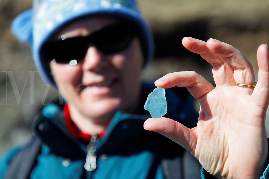 Woman holding shard of blue seaglass, American Camp, San Juan Island National Historical Park, San Juan Island, San Juan County, Washington, USA
